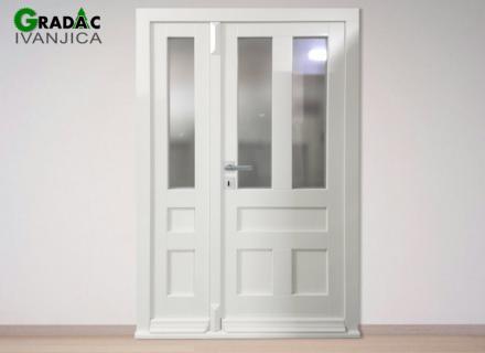 Dvokrilna bela ulazna drvena vrata, u gornjoj polovini peskareno staklo, u donjem delu drveni paneli, pogled sa vanjske strane